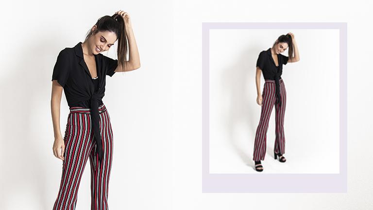 Na foto, clicada em estúdio, temos uma modelo em pé. Ela veste calça flare listrada e camisa preta