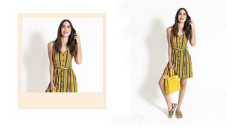 Na foto, clicada em estúdio, temos uma modelo usando vestido listrado colorido