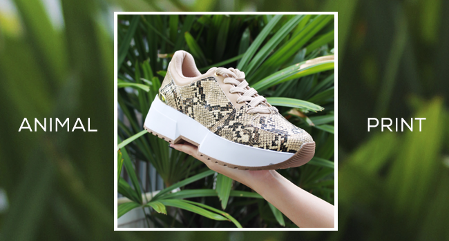O post, com fundo verde desfocado, mostra um dad sneaker com animal print