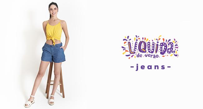 Na foto, clicada em estúdio de fundo branco, temos uma modelo usando blusa amarela e short jeans.