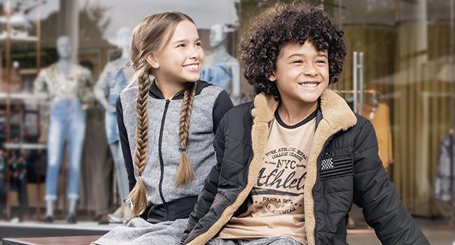 Na foto, clicada em ambiente externo, temos dois modelos infantis sentados. Ela está usando jaqueta e saia e o menino blusa, calça e jaqueta acolchoada.