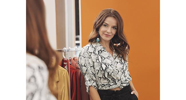 Na foto, temos uma modelo se olhando no espelho. Ela está usando blusa com animal print e calça preta.
