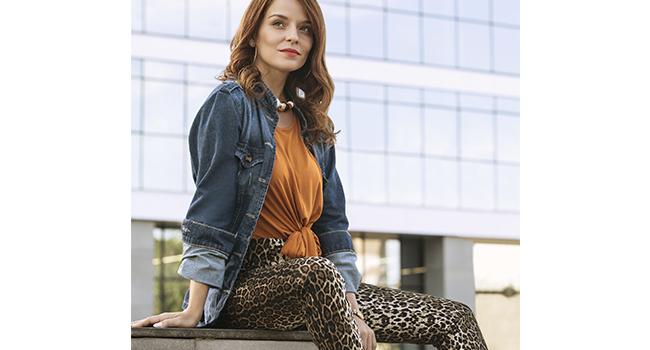 Na foto, clicada em ambiente interno, temos uma modelo sentada. Ela está usando calça com estampa animal print, jaqueta jeans e blusa laranja.