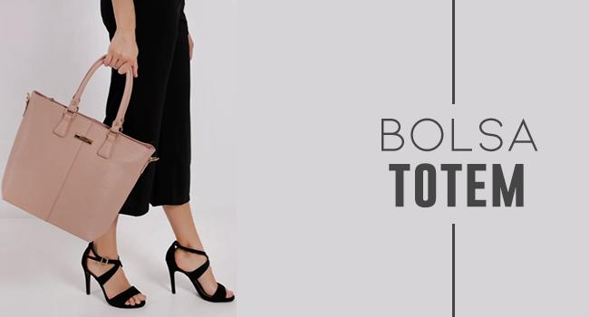 na foto, clicada em estúdio de fundo branco, temos uma modelo de pantacourt preta e sandálias de salto alto preta segurando uma bolsa na cor rosé