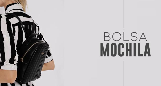 na foto, clicada em estúdio de fundo branco, temos uma modelo de costas usando mochila preta