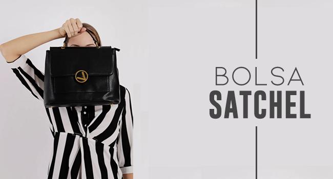 na foto, clicada em estúdio, uma modelo usa vestido listrado e usa bolsa preta em frente ao rosto