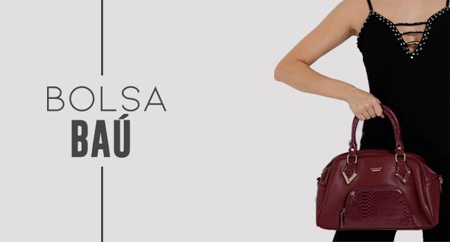 na foto, clicada em estúdio de fundo branco, termos uma modelo usando macacão e segurando uma bolsa de tamanho médio na cor bordô