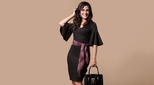 Presentes: na foto, clicada em estúdio de fundo bege, temos uma modelo no centro usando vestido midi preto, lenço na cintura e bolsa preta.
