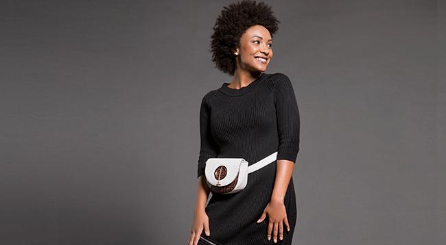 Presentes: na foto, clicada em estúdio de fundo cinza, temos uma modelo usando vestido preto com detalhe na barra e pochete branca.