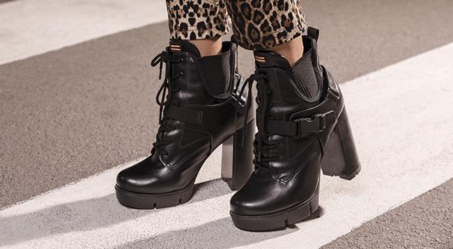 Na foto, clicada em ambiente externo, temos os pés de uma modelo usando coturno de salto alto na cor preta.