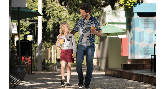 Na foto, clicada em ambiente externo, temos um modelo adulto usando camisa polo estampa e calça jeans. Ele está olhando para uma modelo infantil que usa saia vermelha e blusa clara.