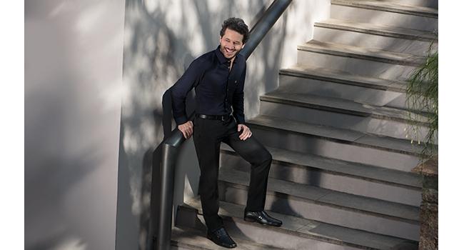 Na foto, clicada em ambiente externo, temos um modelo adulto na escada. Ele está usando calça social preta e uma camisa social azul marinho.