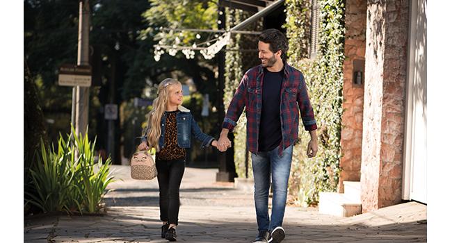 Na foto, clicada em ambiente externo, temos um modelo adulto com camisa azul marinho, camisa xadrez e calça jeans. Ao lado, temos uma modelo infantil usando calça preta, blusa animal print e jaqueta jeans.