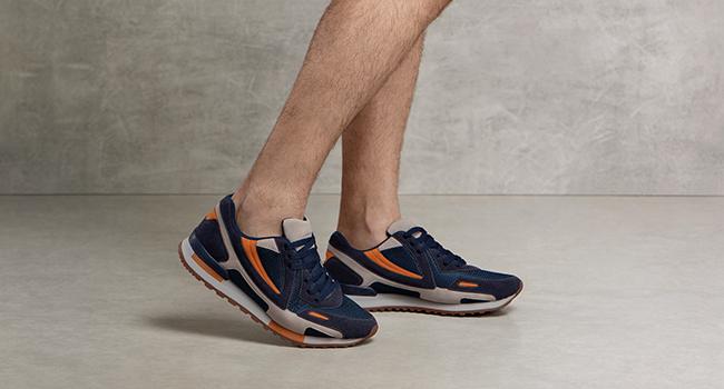 O post é uma foto clicada em fundo cinza. Temos as pernas de um modelo no detalhe. Ele está usando tênis azul marinho com detalhes em bege e laranja,