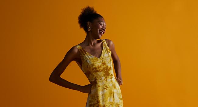 O post é uma foto, clicada em estúdio de fundo laranja, com uma modelo sorrindo e usando vestido estampado.
